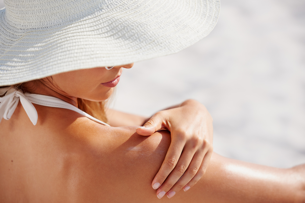 woman applying sunscreen wearing sunhat